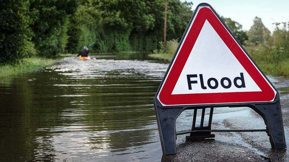 A flood warning sign in front of a flooded road.