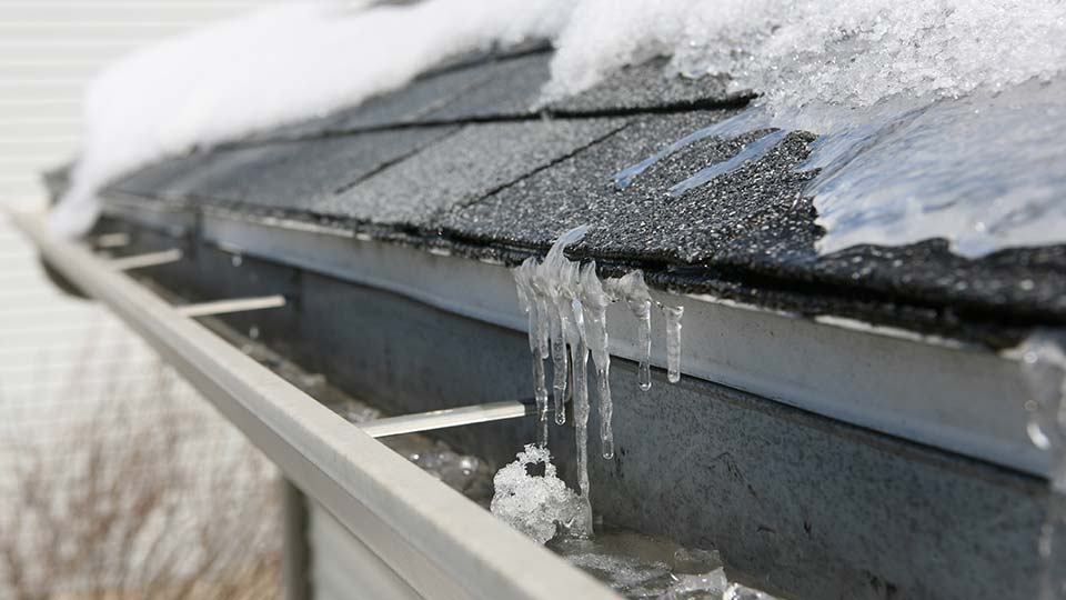 Snow and ice melting on the roof of a building during the winter.