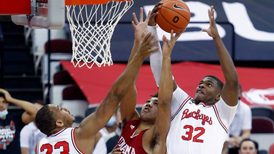 Indiana forward Trayce Jackson-Davis, center, reaches for a rebound between Ohio State forward Zed Key, left, and forward E.J. Liddell during the first half of an NCAA college basketball game in Columbus, Ohio, Saturday, Feb. 13, 2021.