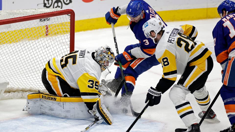 New York Islanders defenseman Adam Pelech (3) has his shot stopped by Pittsburgh Penguins goaltender Tristan Jarry (35) during the second period of an NHL hockey game, Saturday, Feb. 27, 2021, in Uniondale, N.Y.