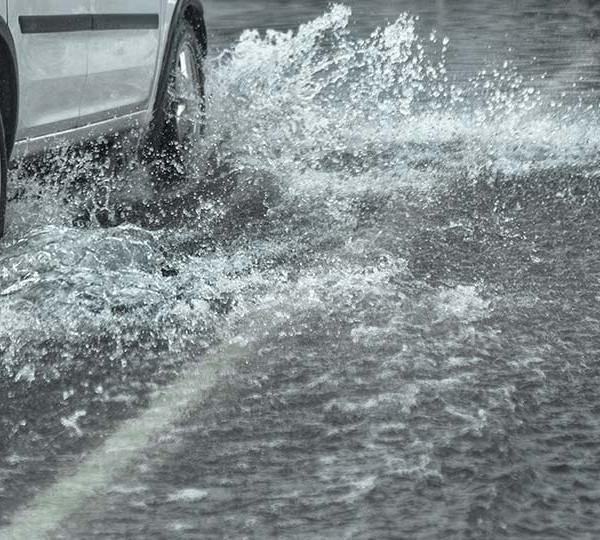 A car driving on a flooded road.