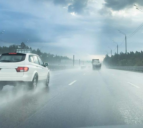 Cars driving on a wet highway road.