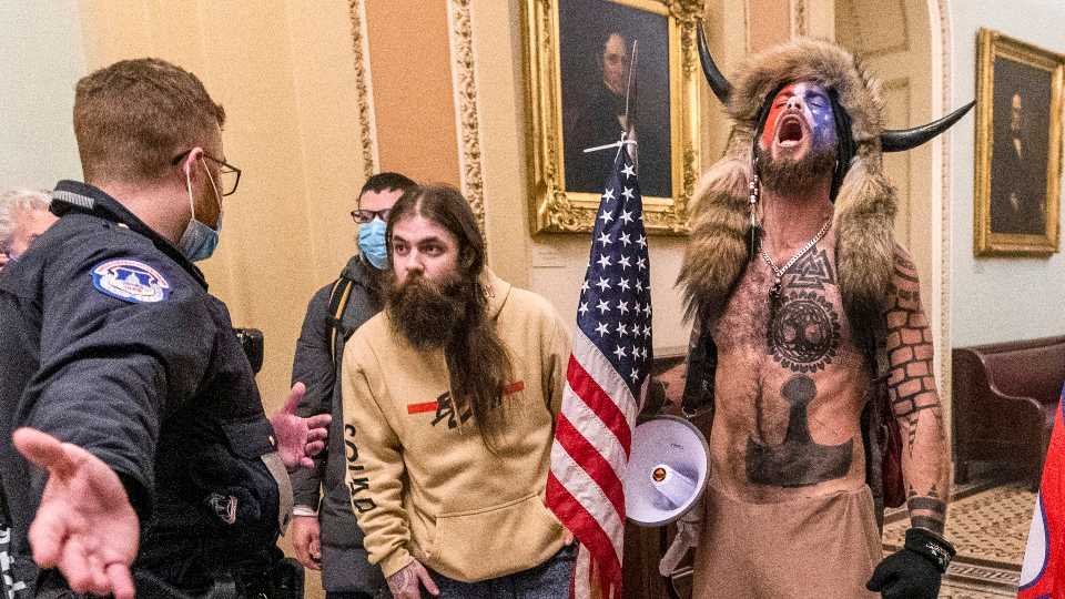 FILE - In this Wednesday, Jan. 6, 2021 file photo, supporters of President Donald Trump, including Jacob Chansley, right with fur hat, are confronted by U.S. Capitol Police officers outside the Senate Chamber inside the Capitol in Washington. A judge ordered corrections authorities to provide organic food to an Arizona man who is accused of participating in the insurrection at the U.S. Capitol while sporting face paint, no shirt and a furry hat with horns