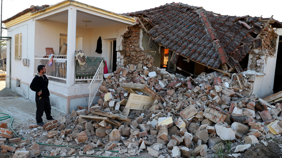 A man stands next to a damaged house after an earthquake in Mesochori village, central Greece