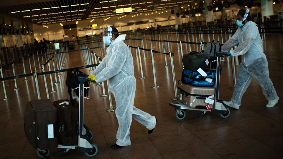 Passengers wearing full protective gear against the spread of coronavirus
