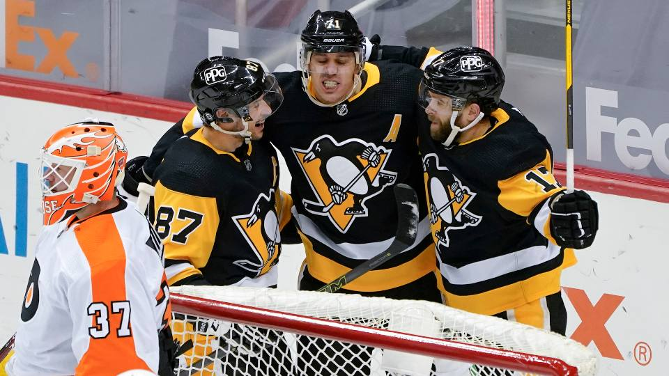 Pittsburgh Penguins' Evgeni Malkin, center, celebrates with Sidney Crosby (87), and Bryan Rust (17) after scoring on Philadelphia Flyers goaltender Brian Elliott (37) during the first period of an NHL hockey game, Saturday, March 6, 2021, in Pittsburgh.