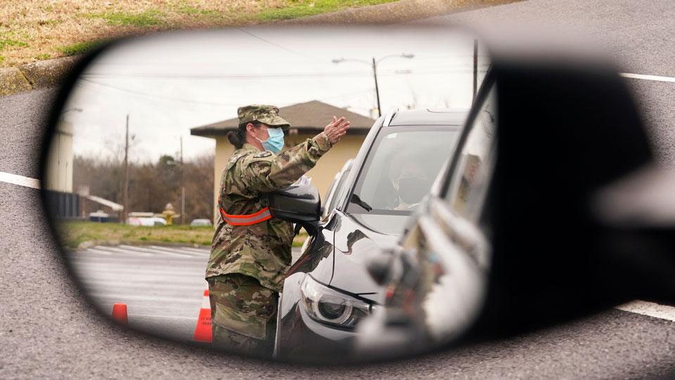 National Guard soldier directing drivers is reflected in the mirror