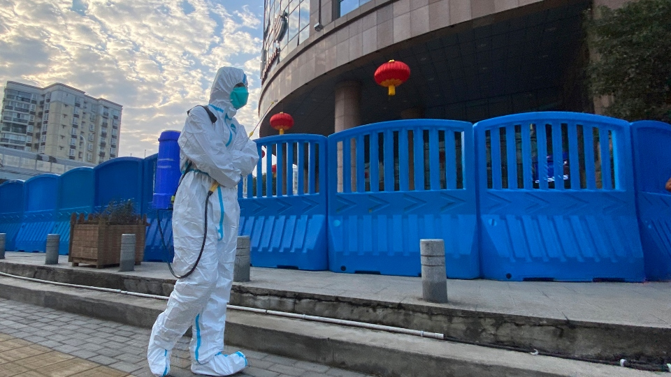 In this file photo dated Saturday, Feb. 6, 2021, a worker in protectively overalls and carrying disinfecting equipment walks outside the Wuhan Central Hospital
