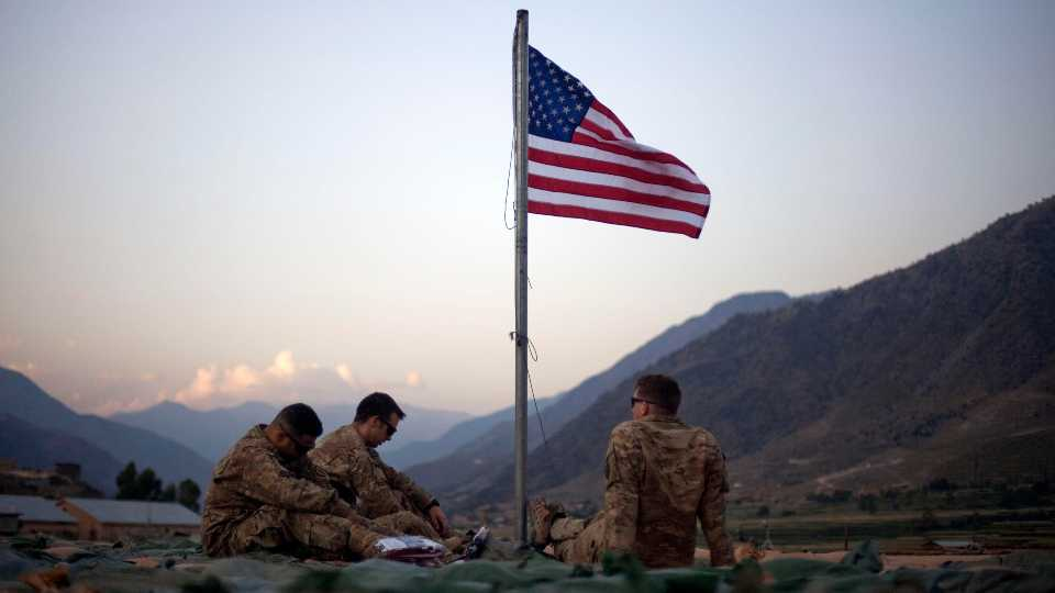 FILE - In this Sept. 11, 2011 file photo, US soldiers sit beneath an American flag just raised to commemorate the tenth anniversary of the 9/11 attacks at Forward Operating Base Bostick in Kunar province, Afghanistan. The Biden administration's surprise announcement in April 2021, of an unconditional troop withdrawal from Afghanistan by Sept. 11, 2021, appears to strip the Taliban and the Afghan government of considerable leverage, pressuring them to reach a peace deal.