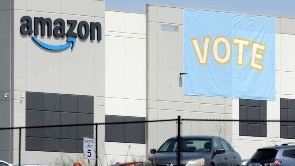 FILE - In this Tuesday, March 30, 2021 file photo, a banner encouraging workers to vote in labor balloting is shown at an Amazon warehouse in Bessemer, Ala. Amazon workers voted against forming a union, Friday, April 9, in Alabama, handing the online retail giant a decisive victory and cutting off a path that labor activists had hoped would lead to similar efforts throughout the company and beyond.