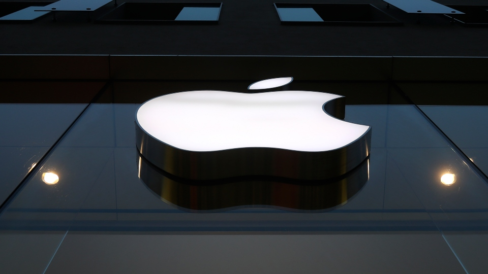 In this Wednesday, Dec. 16, 2020, file photo, the logo of Apple is illuminated at a store in the city center in Munich.