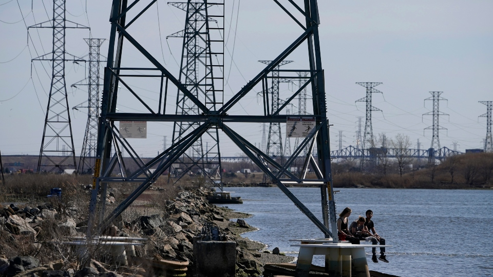People sit at the base of a transmission tower in North Arlington, N.J., Tuesday, April 6, 2021.