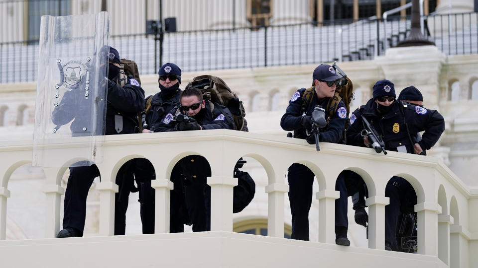 In this Jan. 6, 2021, file photo, police keep a watch on demonstrators who tried to break through a police barrier at the Capitol in Washington.