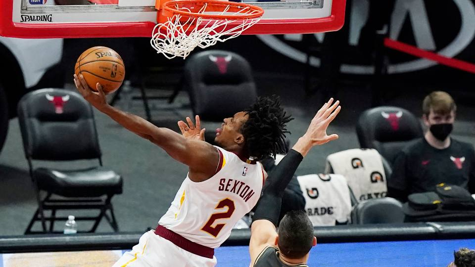 Cleveland Cavaliers guard Collin Sexton, left, drives to the basket against Chicago Bulls center Nikola Vucevic during the first half of an NBA basketball game in Chicago, Saturday, April 17, 2021.