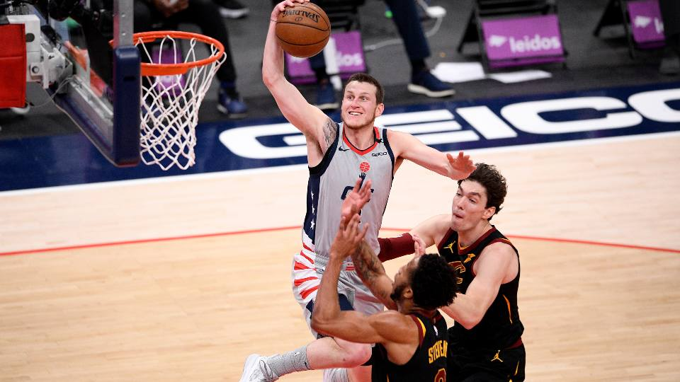 Washington Wizards guard Garrison Mathews, left, goes to the basket against Cleveland Cavaliers forward Lamar Stevens (8) and forward Cedi Osman, right, during the first half of an NBA basketball game, Sunday, April 25, 2021, in Washington. Stevens was called for a foul on the play.