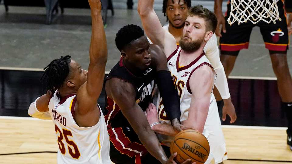 Miami Heat guard Victor Oladipo (4) drives to the basket as Cleveland Cavaliers forwards Dean Wade (32) and Isaac Okoro (35) defend during the second half of an NBA basketball game Saturday, April 3, 2021, in Miami. (AP Photo/Marta Lavandier)