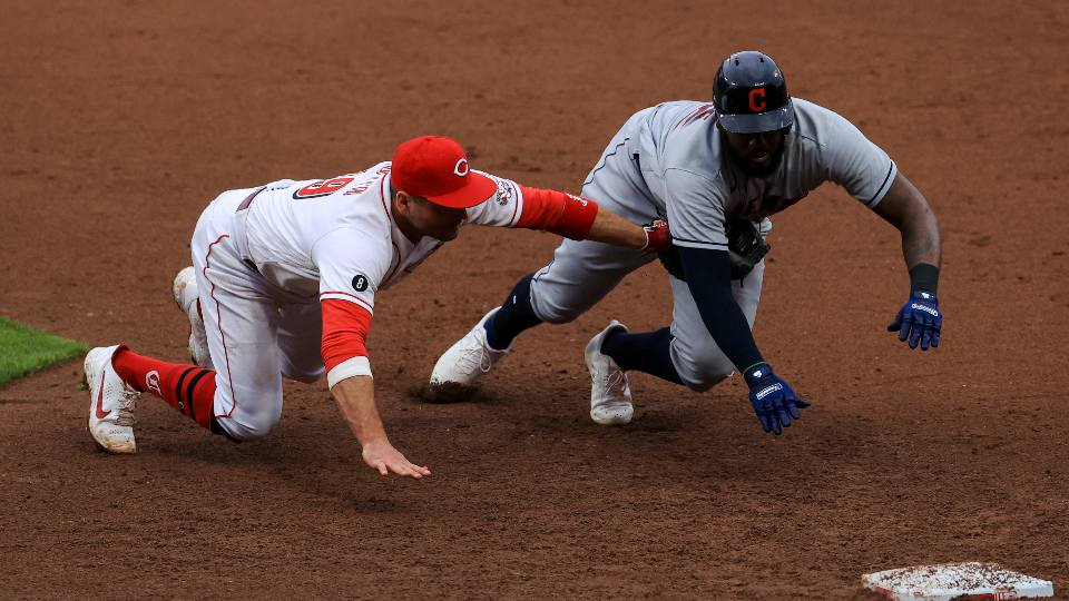 Cincinnati Reds' Joey Votto, left, dives and tags out Cleveland Indians' Franmil Reyes, right, for a triple play during the seventh inning of a baseball game in Cincinnati, Saturday, April 17, 2021. Indians' Josh Naylor lined out to Reds' Joey Votto to start the triple play.
