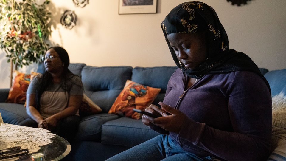 Fatumata Kromah, right, daughter of Rebecca Williams Sonyah, left, browses social media as her mother is interviewed at her home, Thursday, April 22, 2021
