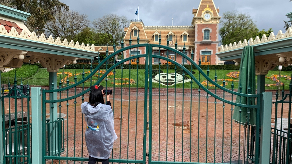 In this March 16, 2020, file photo, a visitor to the Disneyland Resort takes a picture through a locked gate at the entrance to Disneyland in Anaheim, Calif.