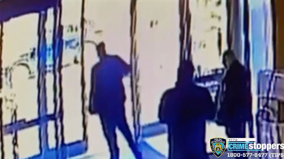 This image taken from surveillance video provided by the New York City Police Department shows an apartment building employee, center, closing the building's front door after a man assaulted a 65-year-old Asian American woman