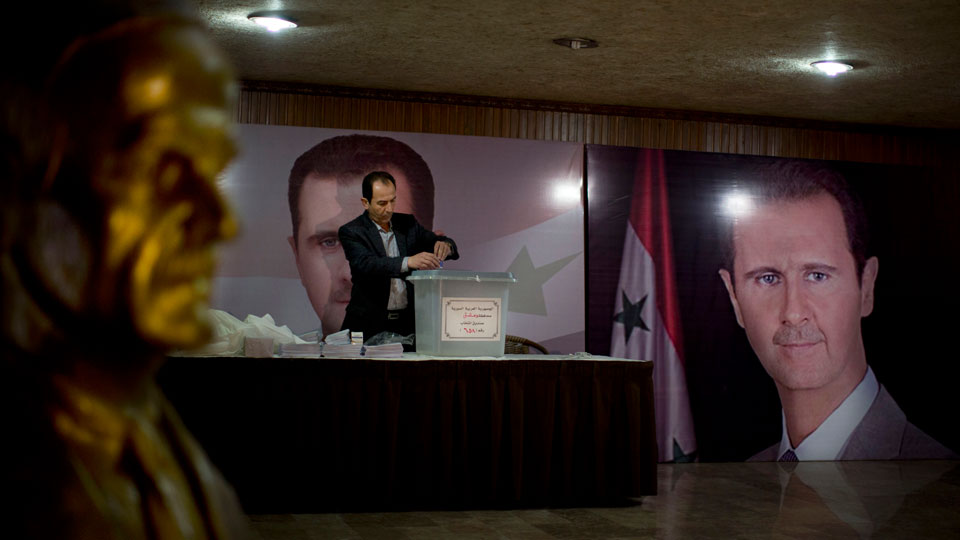 Syrian election official waits for voters at a polling station