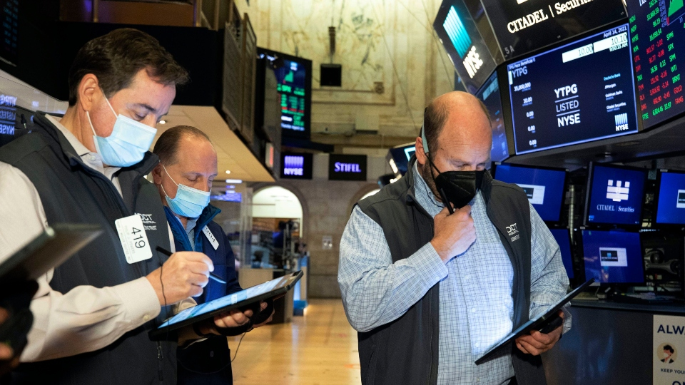 In this photo provided by the New York Stock Exchange, traders work on the floor, Wednesday April 14, 2021.