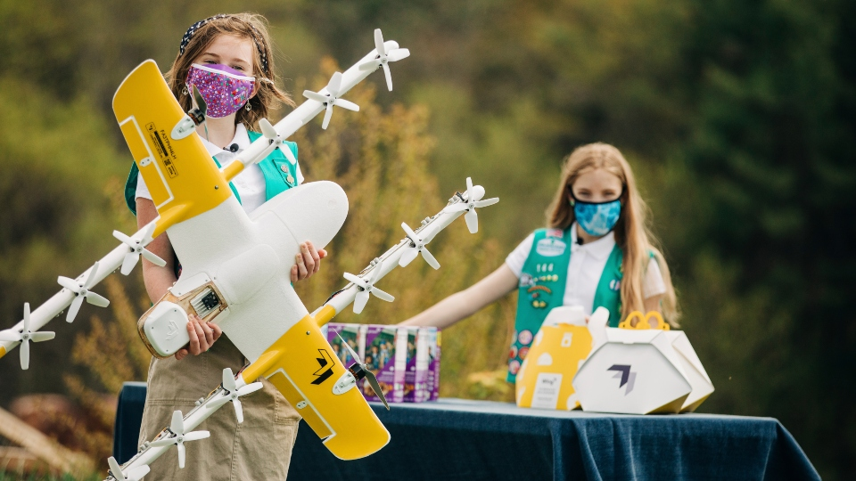 In this April 14, 2021 image provided by Wing LLC., Girl Scouts Alice, right, and Gracie pose with a Wing delivery drone in Christiansburg, Va.