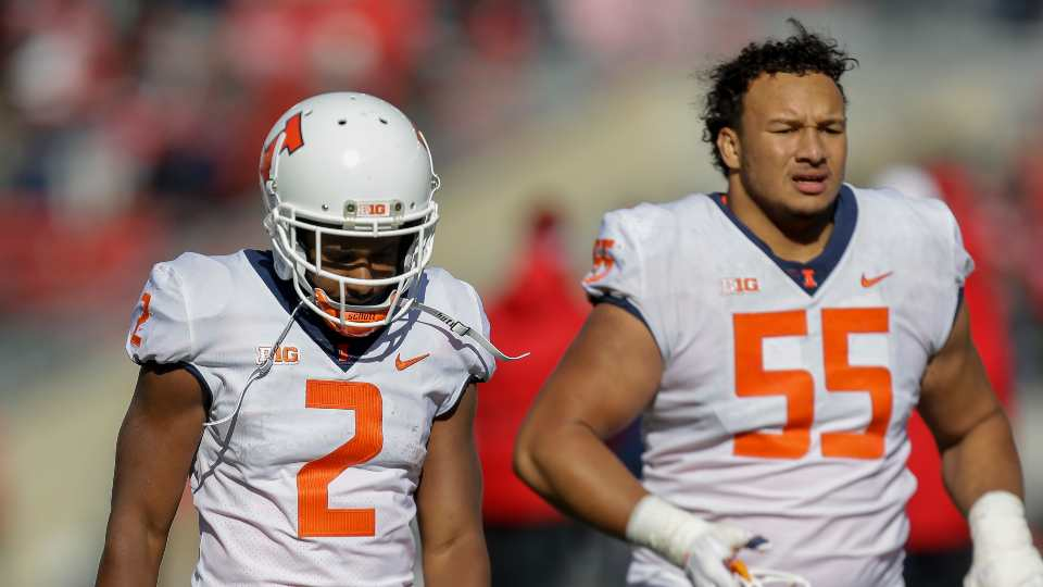 Illinois running back Reggie Corbin (2) and offensive lineman Kendrick Green walk off the field after losing 49-20 to Wisconsin in an NCAA college football game Saturday, Oct. 20, 2018, in Madison, Wis.