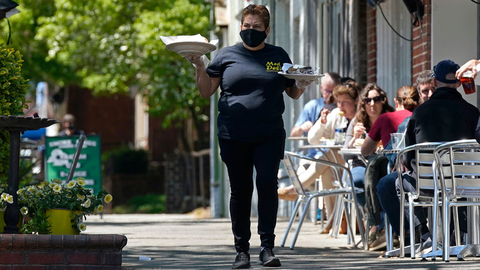 A member of the wait staff delivers food to outdoor diners along the sidewalk at the Mediterranean Deli restaurant in Chapel Hill, N.C., Friday, April 16, 2021