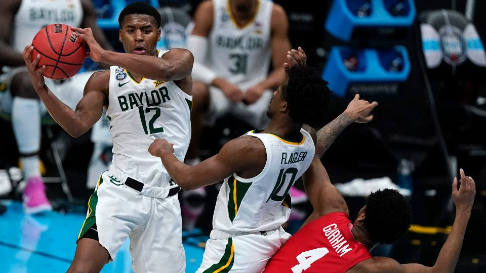 Baylor guard Jared Butler (12) passes over teammate guard Adam Flagler (10) and Houston forward Justin Gorham (4) during the first half of a men's Final Four NCAA college basketball tournament semifinal game, Saturday, April 3, 2021, at Lucas Oil Stadium in Indianapolis.