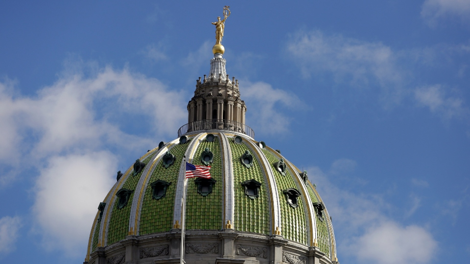 The American flag flies at the Pennsylvania State Capitol building Wednesday Oct. 24, 2018, in Harrisburg, Pa.