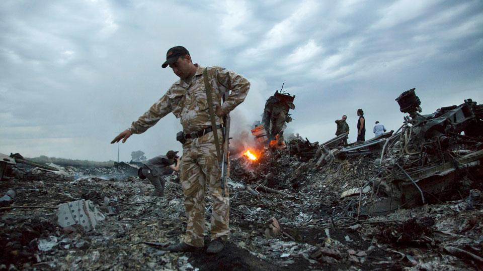 People walk amongst the debris at the crash site of MH17 passenger plane near the village of Grabovo, Ukraine, that left 298 people killed