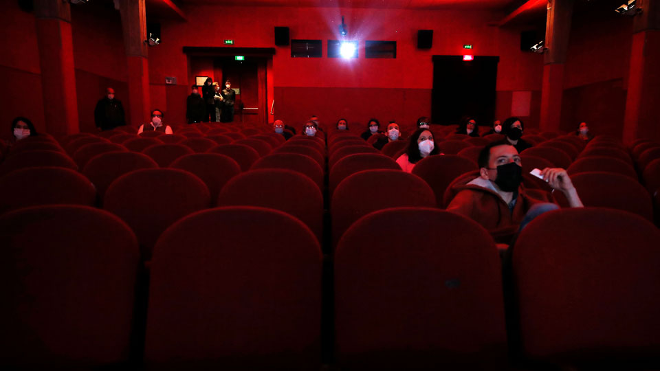 People wear face masks and are distantly seated as they watch a movie inside a cinema hall of the Beltrade cinema, in Milan, Italy, Monday, April 26, 2021