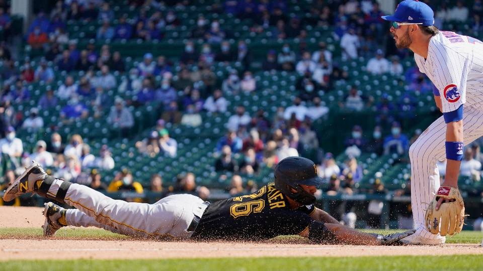 Pittsburgh Pirates' Adam Frazier, left, slides safely into third base after hitting a triple as Chicago Cubs third baseman Kris Bryant waits for the ball during the fifth inning of a baseball game in Chicago, Saturday, April 3, 2021.