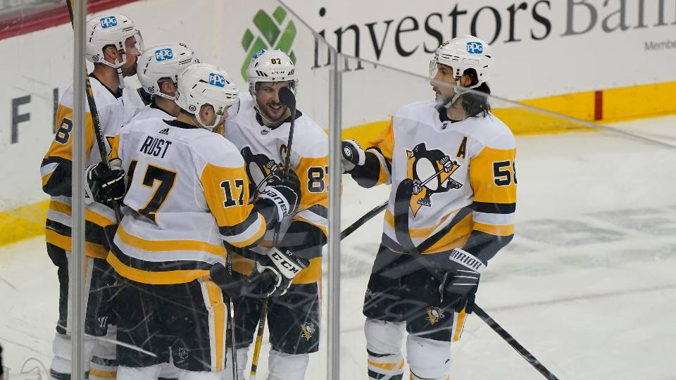 Pittsburgh Penguins center Sidney Crosby (87), and teammates celebrate with right wing Bryan Rust (17) after he scored a goal during the second period of an NHL hockey game against the New Jersey Devils, Sunday, April 11, 2021, in Newark, N.J.
