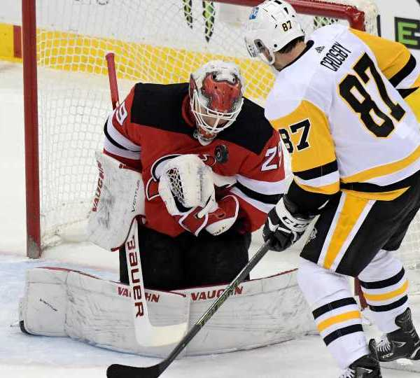 New Jersey Devils goaltender Mackenzie Blackwood (29) stops a shot by Pittsburgh Penguins center Sidney Crosby (87) during the first period of an NHL hockey game Friday, April