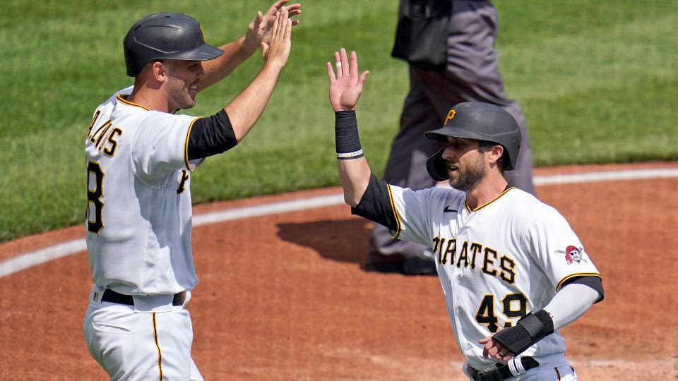 Pittsburgh Pirates' Jacob Stallings, left, and Dustin Fowler, right, celebrate after scoring on a single during the second inning of a baseball game in Pittsburgh, Sunday, April 11, 2021.