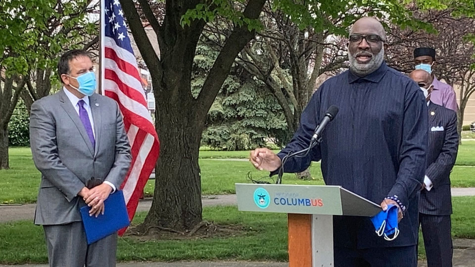Bishop Timothy Clarke of First Church of God in Columbus, right, calls for peaceful protests during a news conference Monday, April 19, 2021, in Columbus, Ohio.