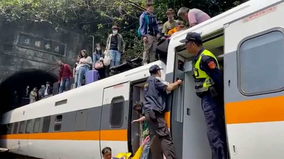 In this image made from a video released by hsnews.com.tw, passengers are helped to climb out of a derailed train in Hualien County in eastern Taiwan Friday, April 2, 2021. The train partially derailed along Taiwan's east coast Friday, injuring an unknown number of passengers and causing potential fatalities.