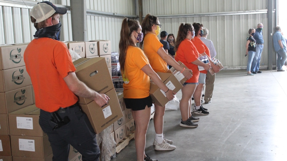 Volunteers wait to load Farmers to Families Food Box packages into cars at a mass distribution site in Westmoreland County, Pennsylvania, on May 26, 2020.