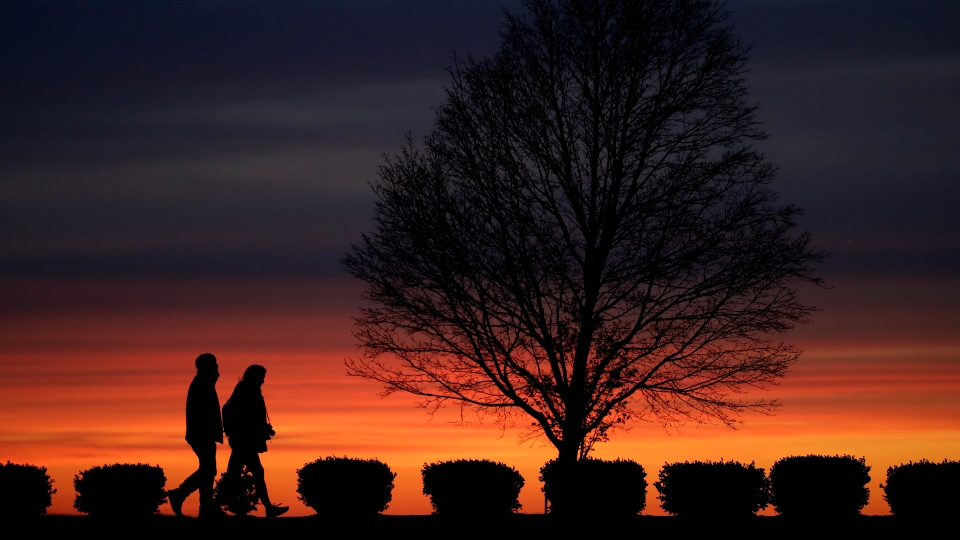 In this Monday, April 13, 2020 file photo, a couple walks alone in a Kansas City, Mo., park at sunset as stay-at-home orders continue in much of the country in an effort to stem the spread of the new coronavirus.