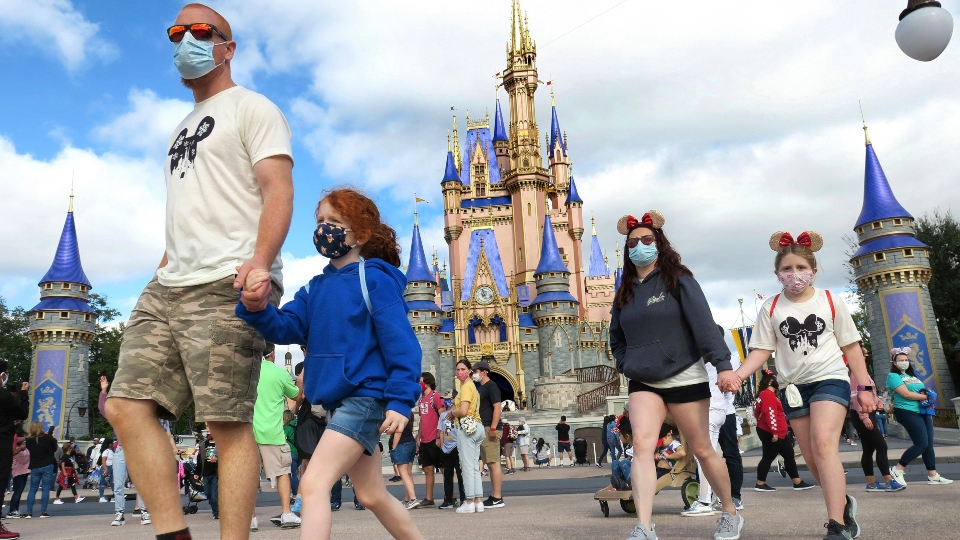 In this Dec. 21, 2020, file photo, a family walks past Cinderella Castle in the Magic Kingdom, at Walt Disney World in Lake Buena Vista, Fla.