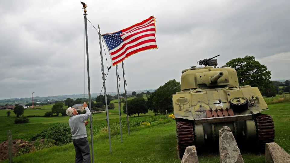 In this Wednesday, July 1, 2020 file photo, Marcel Schmetz raises the US flag next to a WWII American Sherman tank at his Remember Museum 39-45 in Thimister-Clermont, Belgium.