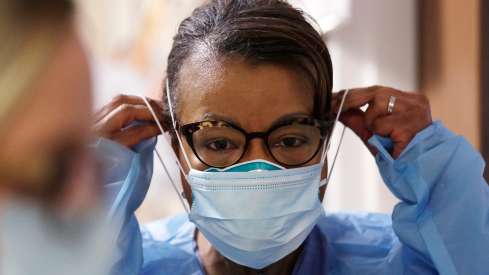 In this Friday, May 8, 2020 file photo, a respiratory therapist pulls on a second mask over her N95 mask before adding a face shield as she gets ready to go into a patient's room in the COVID-19 Intensive Care Unit at a hospital in Seattle.