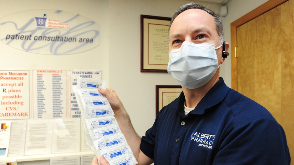 Pharmacist Dr. Joe Albert holds a packet of disposable syringes at Albert's Pharmacy in Pittston, Pa., Monday April 12, 2021.