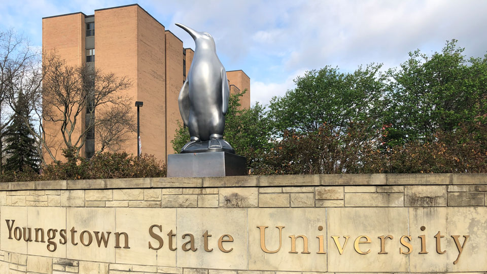 A penguin statue and sign at 1 University Plaza on Youngstown State University campus