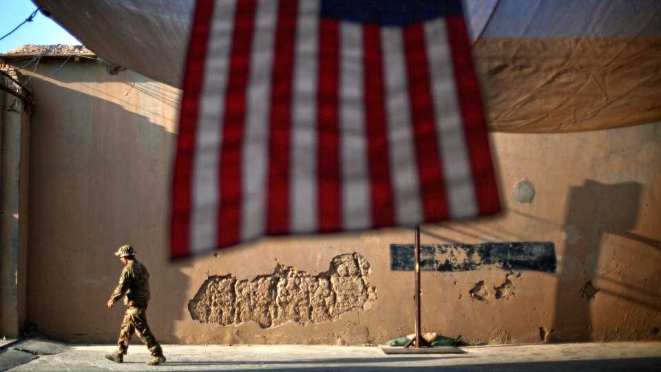 """FILE - In this Sept. 11, 2011 file photo, a U.S. Army soldier walks past an American Flag hanging in preparation for a ceremony commemorating the tenth anniversary of the 9/11 attacks, at Forward Operating Base Bostick in Kunar province, Afghanistan. The final phase of ending America's """"forever war"""" in Afghanistan after 20 years formally began Saturday, May 1, 2021, with the withdrawal of the last U.S. and NATO troops by the end of summer."""
