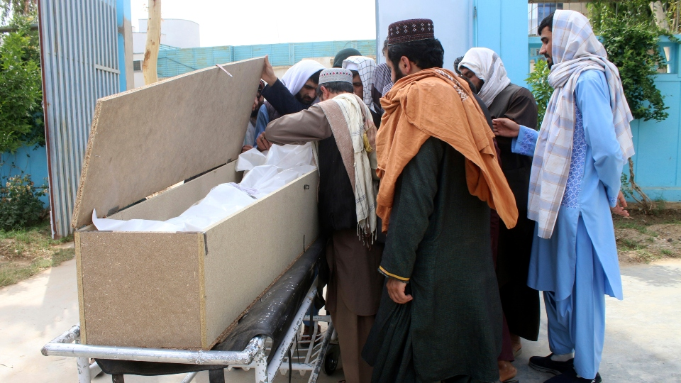 Afghans mourn over the body of Nimat Rawan, a former Afghan TV presenter, at a hospital in Kandahar, Afghanistan, Tuesday, May 6, 2021.