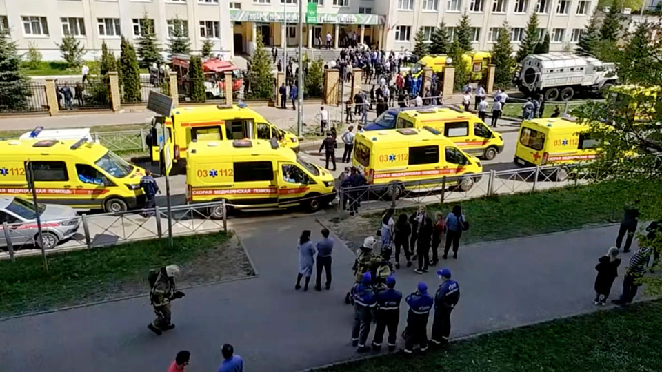 Ambulance and police trucks are parked at a school after a shooting, in Kazan, Russia