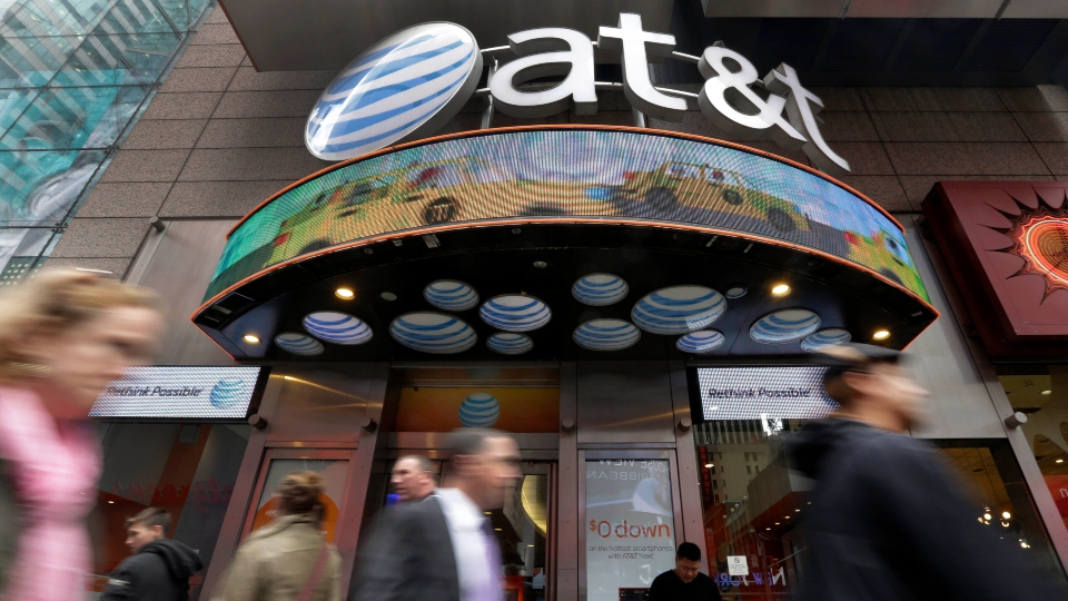 In this Oct. 21, 2014 file photo, people pass an AT&T store in New York's Times Square.